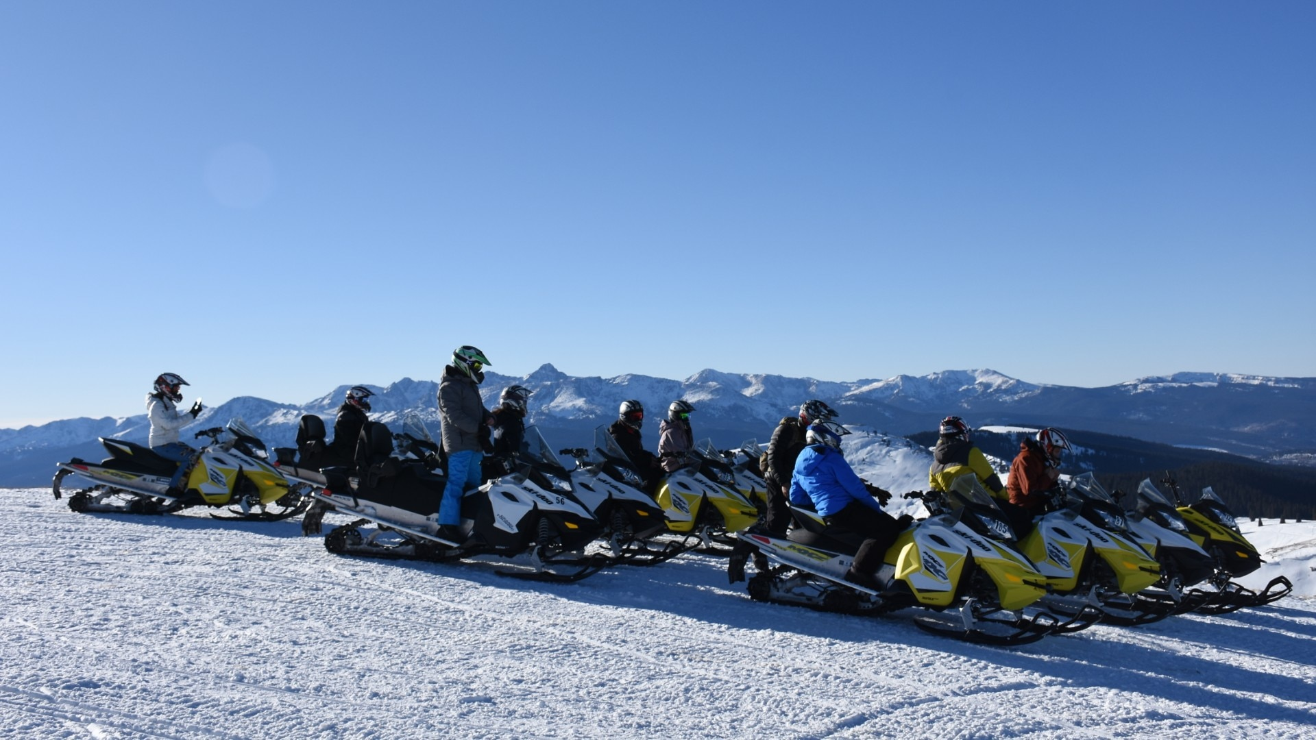Group snowmobiling on top of the rockies